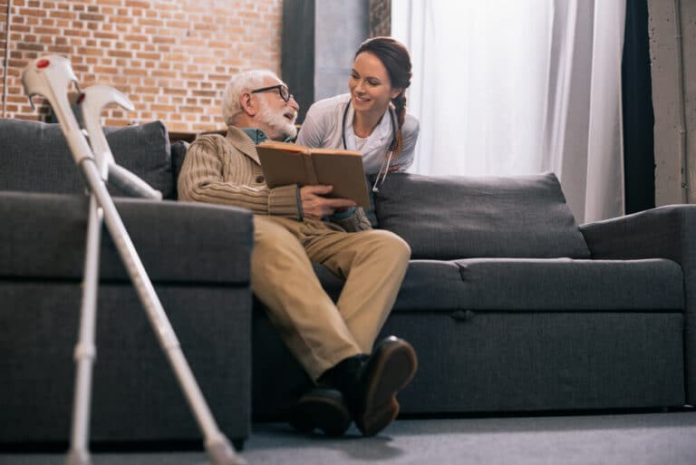 #Pracegover foto: na imagem há uma mulher, um idoso, sofá, livro e muletas