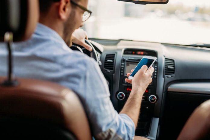 #Pracegover foto: na imagem há um homem dirigindo e segurando o celular