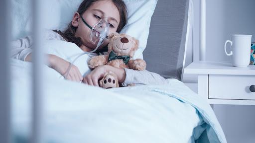 #Pracegover foto: na imagem há uma criança com um respirador, um urso de pelúcia e uma cama