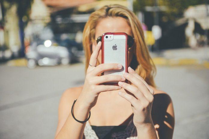 #Pracegover foto: na imagem há uma mulher com um celular