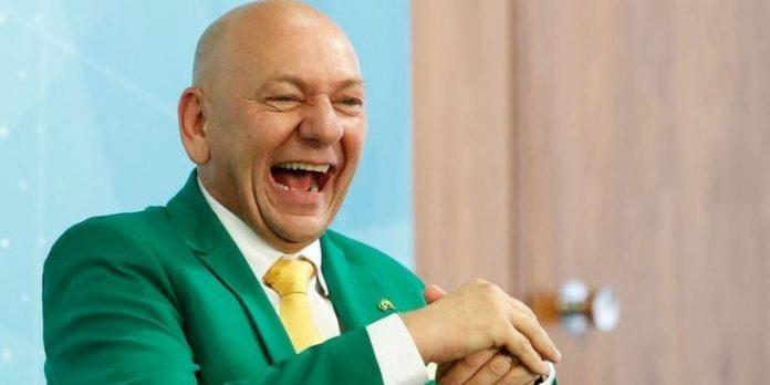 #Pracegover foto: na imagem há um homem de terno verde, camisa branca e gravata amarela