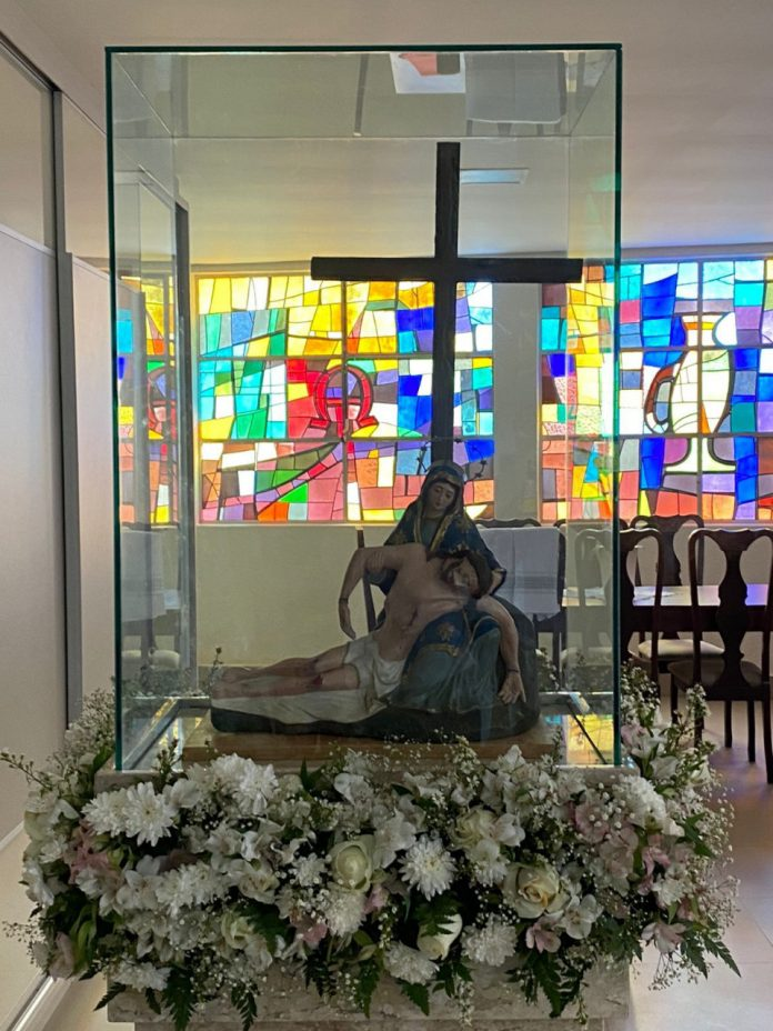 #Pracegover foto: há imagens de santos católicos, flores, uma cruz e cadeiras