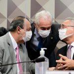 #Pracegover foto: na imagem há 3 homens de terno e com máscara, microfone e um frasco de álcool em gel
