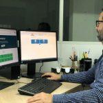 #Pracegover foto: na imagem há computadores, um homem e materiais de escritório