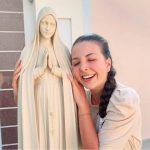 #Pracegover foto: na imagem há uma jovem abraçando uma santa