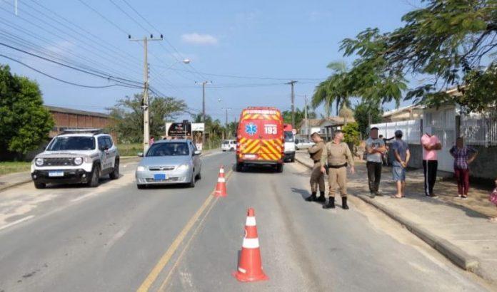 #Pracegover foto: na imagem há uma via, pessoas, carros, cones e árvores