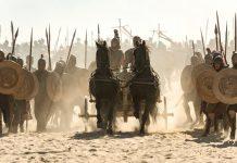 #Pracegover foto: na imagem há cavalos, homens e armas
