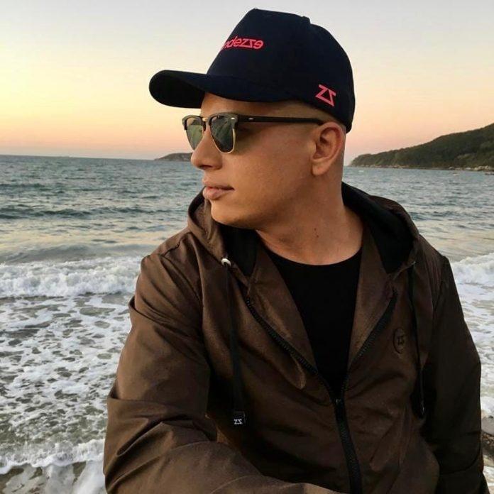 #Pracegover foto: na imagem há um homem de roupa escura, um boné escuro, de óculos escuro e o mar