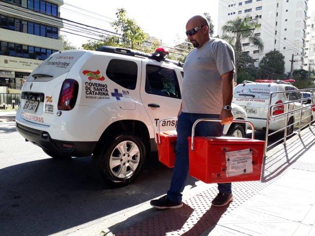 #Pracegover foto: na imagem há um homem com maletas, carros, via e prédios
