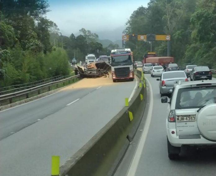 #Pracegover foto: na imagem há carros, caminhões, um deles tombado, pistas de rodovia e árvores