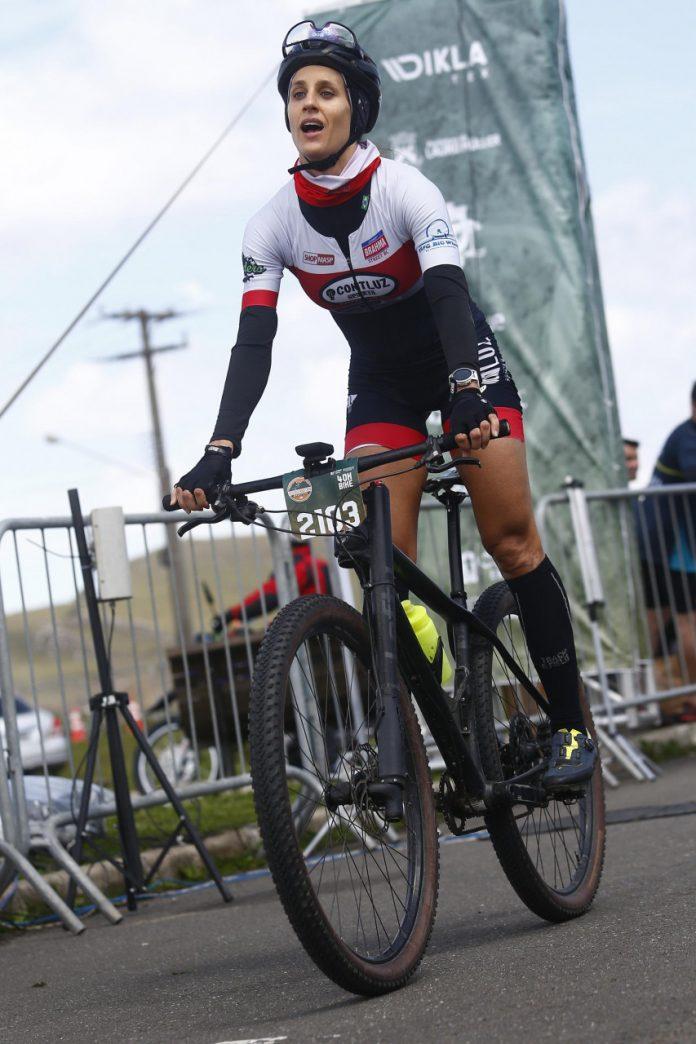 #Pracegover foto: na imagem há uma mulher com capacete e roupa esportiva em uma bicicleta