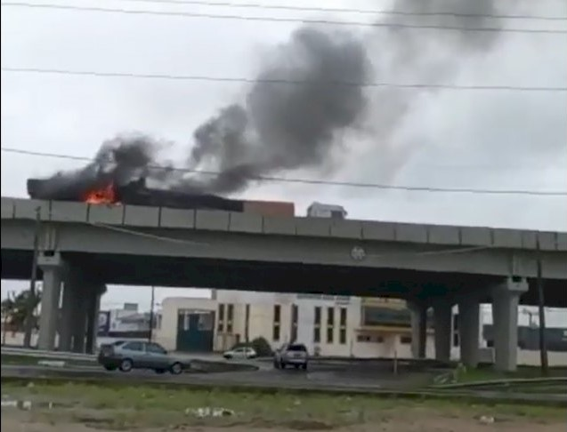 #Pracegover foto: na imagem há uma via, carros e uma carreta pegando fogo