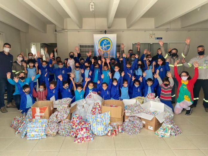 #Pracegover : na imagem há diversas pessoas, a maioria com uniforme azul e muitos brinquedos