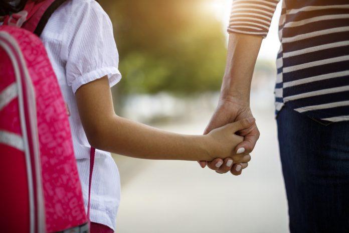 #Pracegover foto: na imagem há uma mulher com um menina de mãos dadas