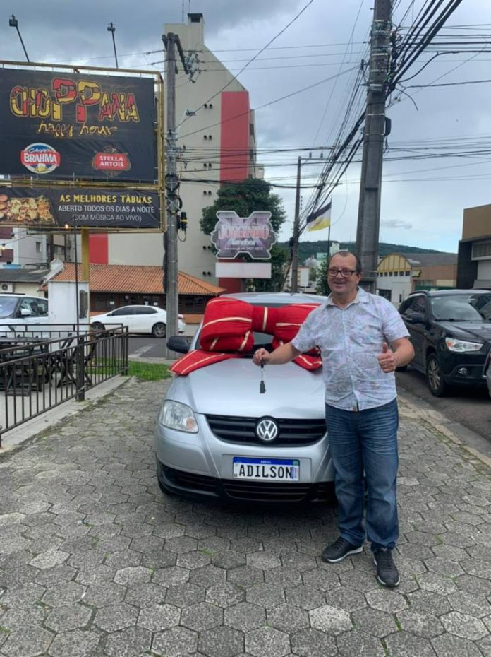 #Pracegover foto: na imagem há um homem, veículos e prédios