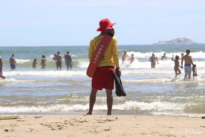 #Pracegover foto: na imagem há pessoas, mar e areia