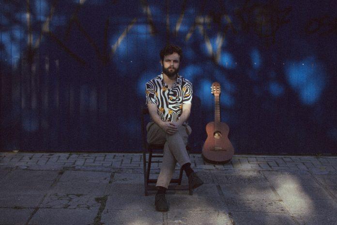 #Pracegover foto: na imagem há um homem sentado em uma cadeira e um violão