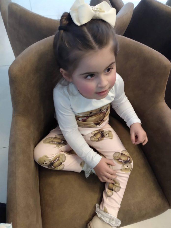 #Pracegover foto: na imagem há uma menina de três anos sentada em um sofá