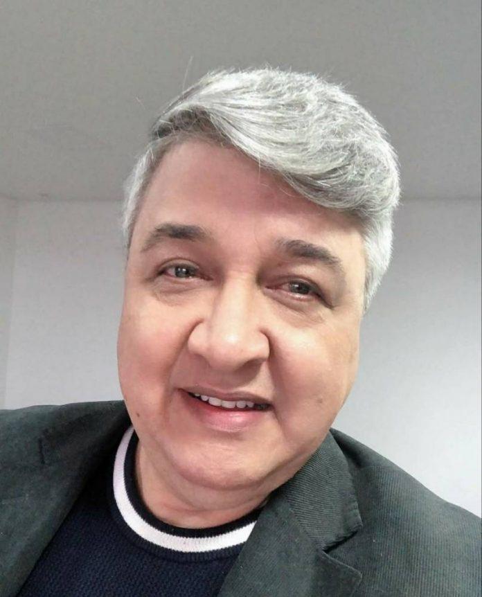 #Pracegover foto: na imagem há um homem com roupa escura e cabelos grisalhos