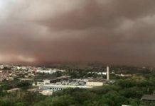 #Pracegover foto: na imagem há um céu escuro, casas, prédios e árvores