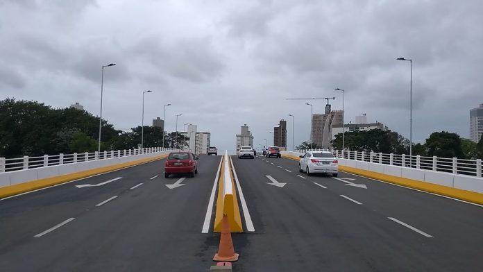 #Pracegover foto: na imagem há uma ponte, veículos, postes e prédios
