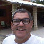 #Pracegover foto: na imagem há um homem de camiseta branca, óculos e ele está sorrindo. O homem está próximo a uma casa de alvenaria